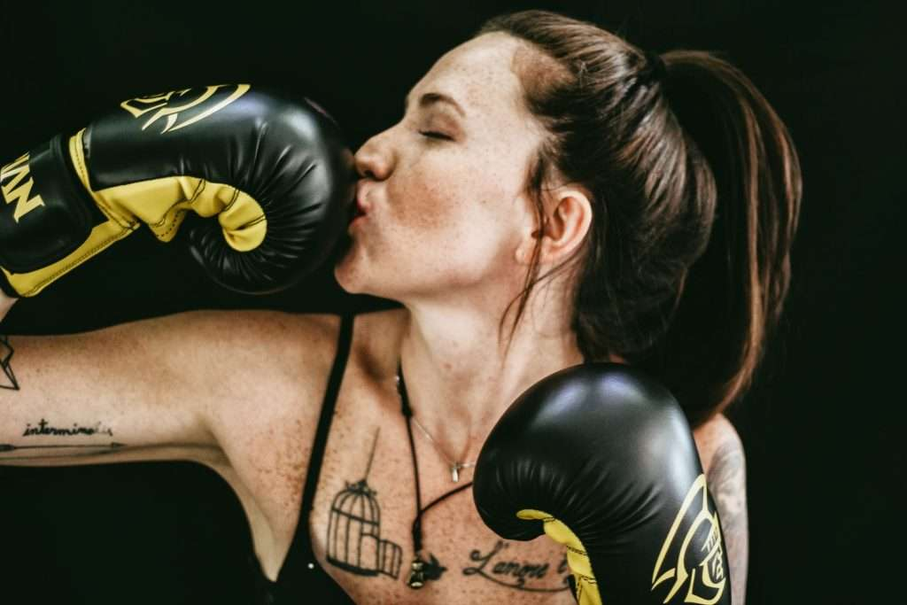 Woman boxer kissing her glove because she knows how to master resilience