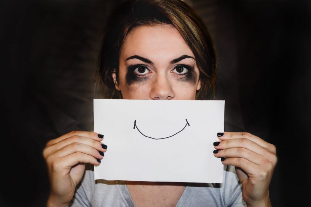 Sad Woman trying to be a successful positive thinker holding up a hand-drawn smile