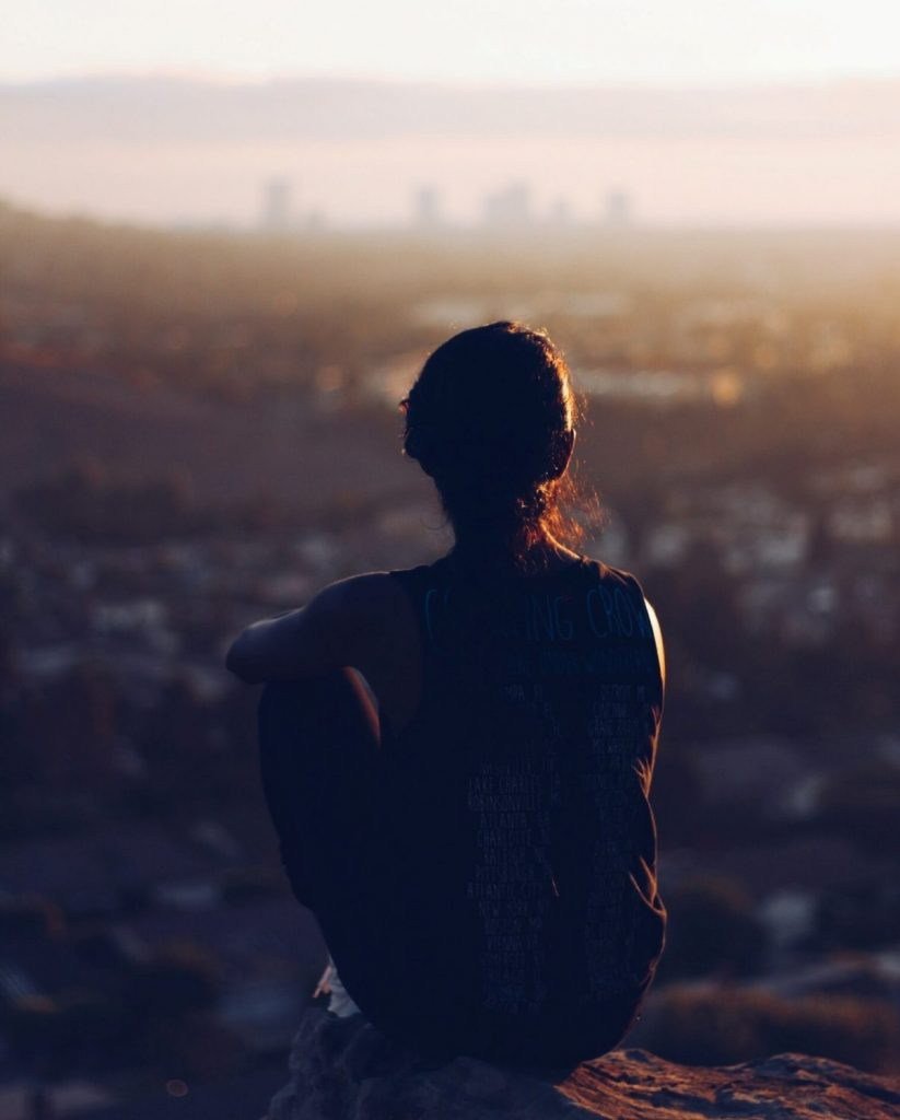 Woman on a hillside gazes across the city. She's found inner peace to manage stress